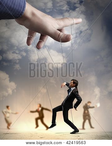Businesspeople marionette on ropes controlled by puppeteer