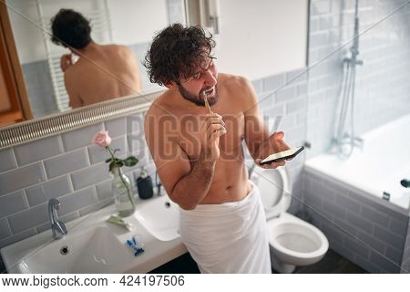 young caucasian male looking at his cell phone while brushing teeth in the bathroom. modern adiction