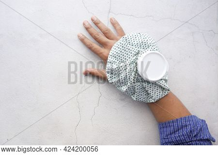 Young Man Hands Suffering Wrist Pain, And Applying Cold Water On Injury Spot