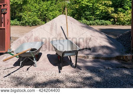 A Large Pile Of Sand Mixture Lies In The Doorway. Two Construction Wheelbarrows And Shovels Stand Ne