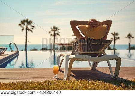 Rear View Woman Wear Hat Lying On Deckchair Near Pool, Put Hands Behind Head Relaxing, Take Sun Bath