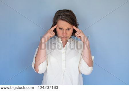 Thoughtful Focused Woman Tries To Remember Something In Mind, Poses Against Blue Wall.