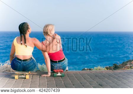 Girls Sit On Their Skateboards Near Of The Beach. Young Sporty Friends Having Fun In Summer Vacation