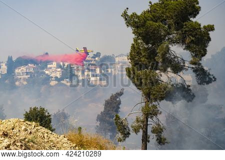 Mevasseret Zion, Israel - June 19th, 2021: A Firefighter Airplane Drops Flame Retardant Over A Pine