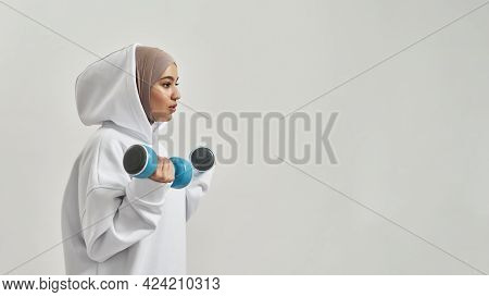 Attractive Young Arabian Woman In Hijab And Hoodie Holding Dumbbells While Posing Sideways On Light