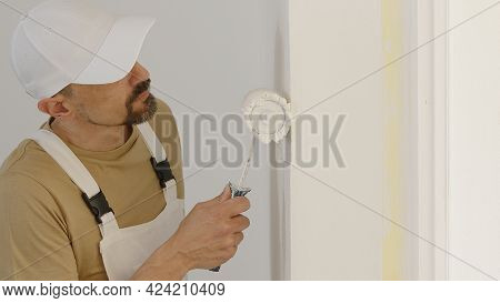 Hand Of Painter Man Decorator Work Of House To Renovate, Using Roller Paint, Window Fixture As Backg