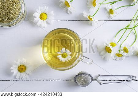 Close-up Top View Of A Cup Of Chamomile Tea, A Can Of Dry Raw Materials And A Spoon For Infusion. Al