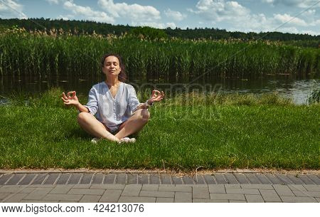 Young And Serene Woman Sitting On The Green Grass In Lotus Position And Meditating On The River Bank