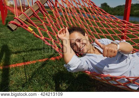 Relaxed Woman Lying In A Hammock And Smiling Cutely With Toothy Smile At The Camera And Showing A Th