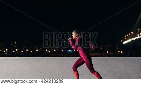 Young Female Jogger Exercising In The Evening. Woman Running At Embankment.