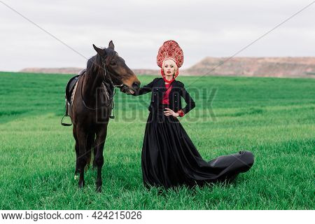 Blonde Slavic Female In Black Dress And Headdress On Field With A Black Horse At Sunset