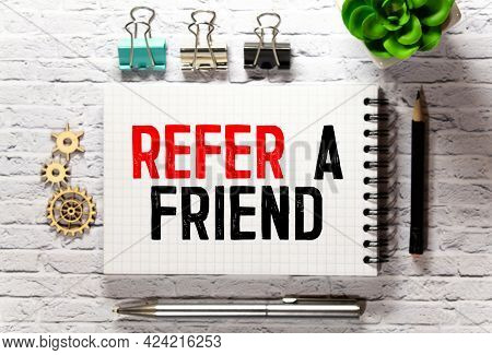 Text Refer A Friend Written On The White Paper With Pen And A Cup Of Coffee Aside