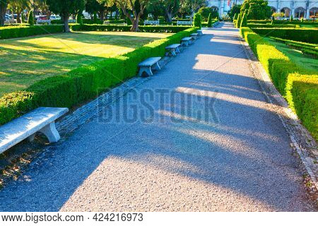 Walking Path Of Praca Do Imperio In Lisbon . Monumental Green Space With Stone Benches Near Jeronimo