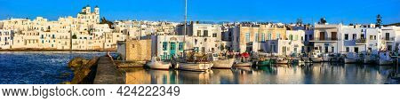 Greece travel. Cyclades, Paros island. Beautiful fishing village Naousa. Panorama of old port with sailing boats over sunset. may 2021
