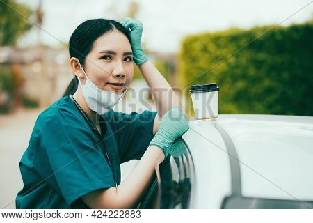 Portrait Of Tired Exhausted Nurse Or Doctor Having A Coffee Break Outside In The Morning. Covid-19,