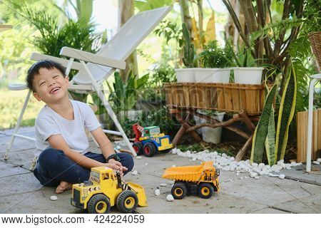 Cute Asian Young Kindergarten Boy Playing With Pebbles And Toy Construction Machinery, Happy Smiling