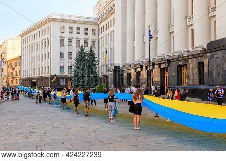 Kiev, Ukraine - August 23, 2019: People Holding A Huge Ukrainian Flag Near Presidential Administrati