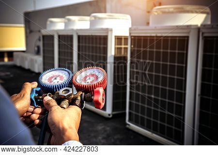 Close-up Engineer Using Measuring Manifold Gauge For Filling Industrial Air Conditioner After Cleane