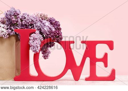 Bouquet Of Lilac Flowers In A Bag And A Red Love Word On Pink. Spring Valentines Or Mothers Day Gree