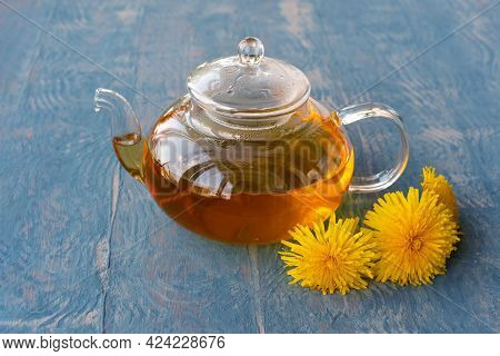Glass Transparent Teapot With Healthy Herbal Tea Near A Bouquet Of Yellow Dandelions On A Blue Woode