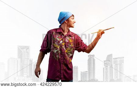 Young Male Artist Holding Paintbrush. Happy Painter In Dirty Shirt And Bandana Standing On Backgroun
