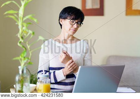 Woman Teleworking From Home With Wrist Pain Having A Massage To Rest.