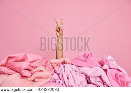 Indoor Shot Of Humans Hand Gesturing Peace Sign Near Stack Of One Toned Unfolded Clothes Against Pin