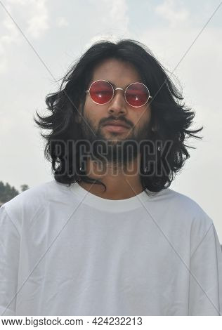 Front View Of A Long Haired Indian Young Men Wearing Sunglasses With Looking At Camera, A Good Looki