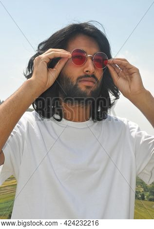 A Long Haired Young Men Wearing Sunglass With His Hands With Looking Sideways, A Good Looking Bearde