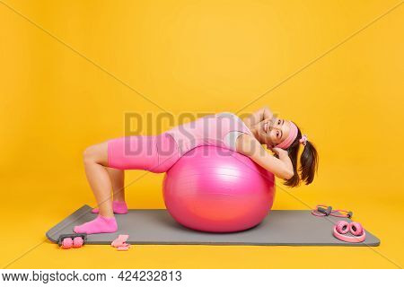 Energetic Slim Asian Woman With Glad Expression Leans Over Fitness Ball Has Hapy Expression Does Pil