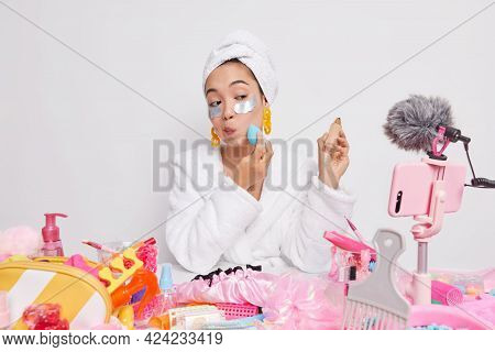 Serious Woman Looks Attentively At Camera Of Mobile Phone Applies Foundation On Face With Sponge Bea