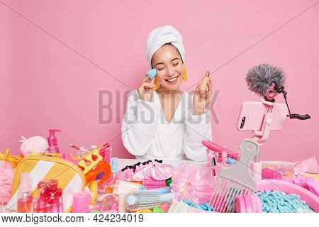 Happy Pretty Asian Woman Applies Foundation On Face Records Video About Cosmetics Smiles Pleasantly