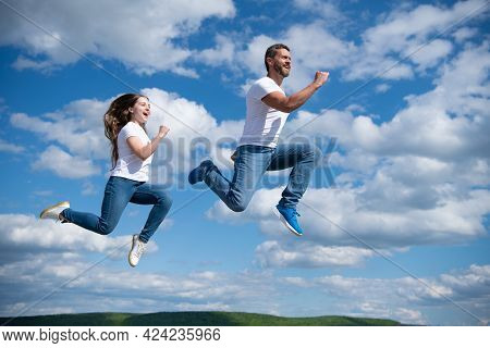 Father And Daughter Jump High. Hurry Up. Happy Childhood And Fatherhood. Concept Of Friendship