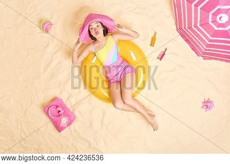 Funy Summer Asian Girl Keeps Lips Folded Keeps Hands On Pink Sunhat Sunbathes During Hot Day Has Fun