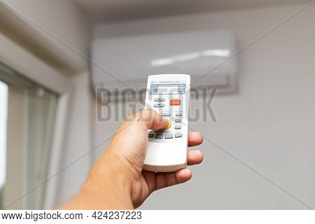 Close-up Of Men Hand Holding Air Conditioner Remote Control