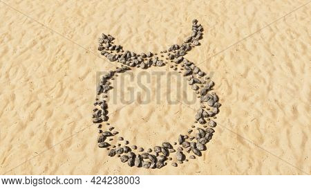 Concept conceptual stones on beach sand handmade symbol shape, golden sandy background, taurus zodiac sign. 3d illustration symbol for  esoteric, the mystic, the power of prediction of astrology