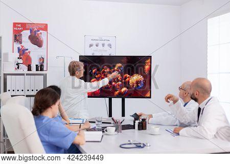 Senior Woman Virolog Presenting Virus Evolution Pointing On Monitor During Coworkers Meeting Working