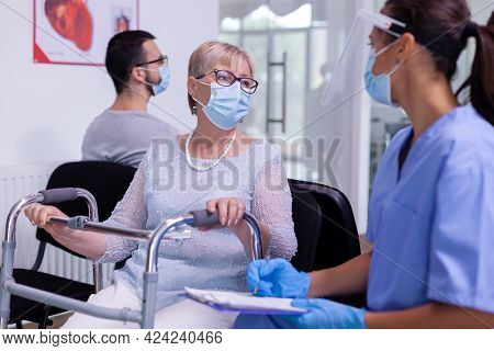 Nurse With Protection Mask Against Infection With Coronavirus Explaining Diagnosis To Disabled Senio