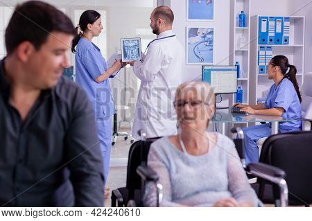 Doctor Holding Patient X-ray Explaining Diagnosis To Nurse In Waiting Area. Disabled Senior Woman Wh