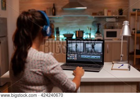 Brunette Video Editor Works With Footage On Personal Laptop In Home Ktichen During Night Time. Conte