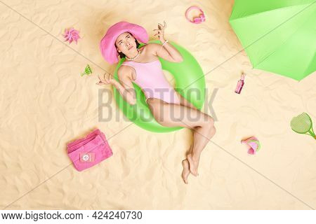 Overhead Shot Of Displeased Puzzled Asian Lady Raises Hands With Indignant Expression Lies On Inflat