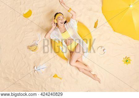 Overhead Shot Of Cheerful Young Asian Woman Enjoys Listening Favorite Music Wears Wireless Headphone