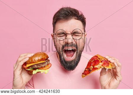 Emotional Bearded Man Eats Junk Food Shouts Loudly Keeps Mouth Widely Opened Holds Burger And Slice