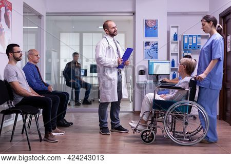 Paralyzed Disabled Elderly Woman In Wheelchair Visiting Specialist Doctor For Period Checkup. Happy