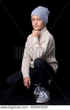 Portrait Of Cute Teenage Boy Squatting. Handsome Stylish Boy Knitted Jumper Posing In Studio Against