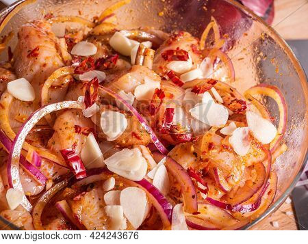 Cooking Asian-style Chicken. Chopped Chicken Breast In A Bowl With Hot Sauce And Chopped Onions And
