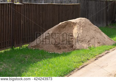 Pile Of A Sand On The Green Lawn Near A Fence Of A Country House In Summer