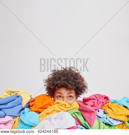 Young Afro American Woman Surrounded By Different Colorful Clothes Sorts Out Wardrobe Focused Above