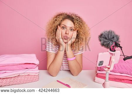 Lovely Woman Blogger Keeps Lips Folded Hands On Face Sits At Table Near Smartphone On Tripod Records