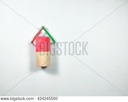 Colorful Paper Clips And Block Cylinders Arranged Like A House On A White Background With Copy Space